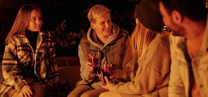 friends with mulled wine at bonfire in garden