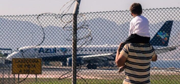 Man carrying his child overlooking an airplane