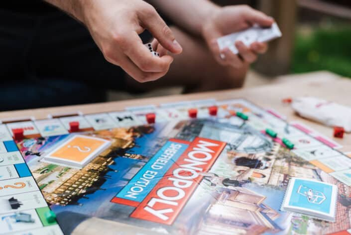 Faceless man preparing to roll dices while playing board game