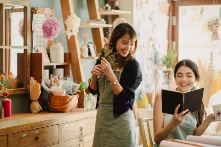 two girls smiling while the other one is reading something from a black notebook
