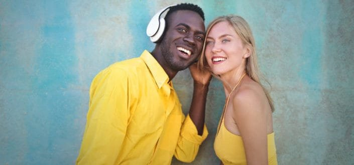 woman trying to hear the sound from a man's headphones