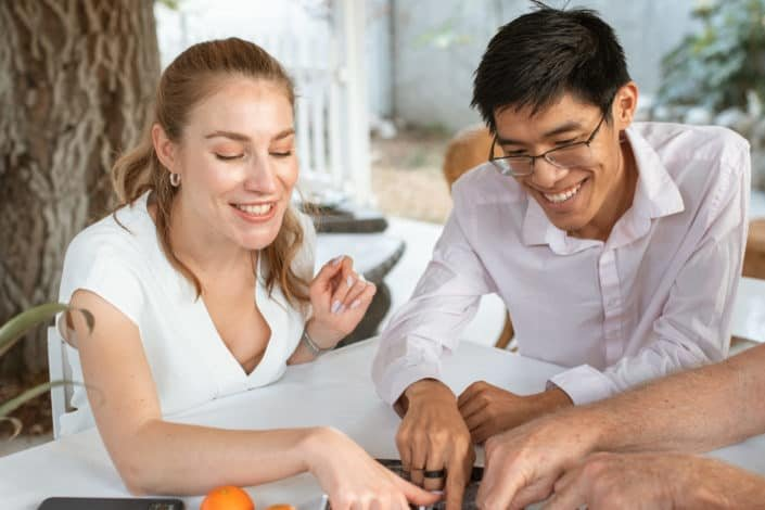 man and woman both wearing white pointing at something on a table