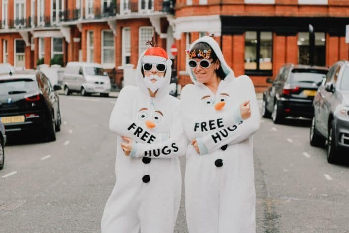 two people wearing white snowman overalls with free hugs print