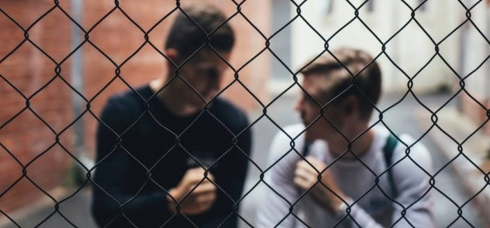 two men behind a wire fence