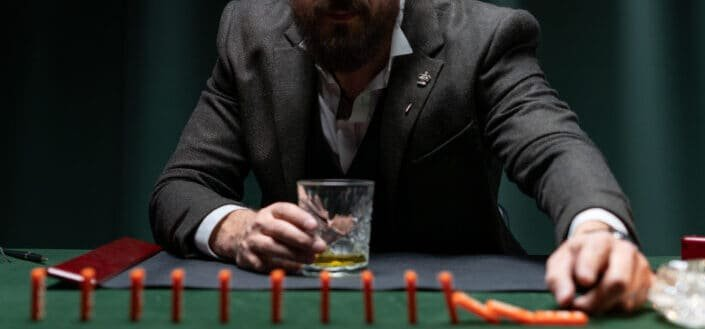 man holding a glass of bear playing dominoes