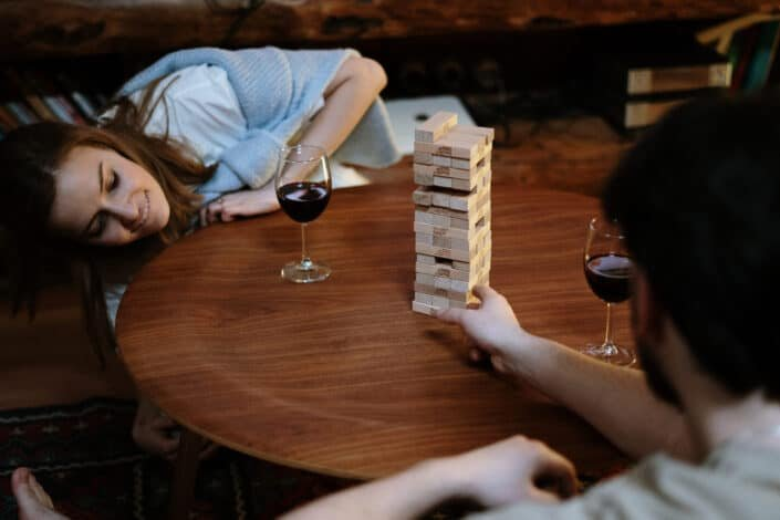 man and woman playing jenga over a glass of wine
