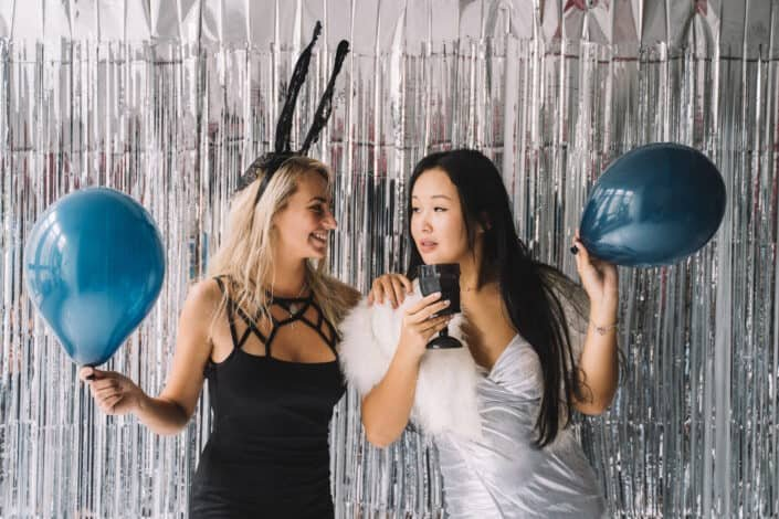 two women holding balloons in a festive setting