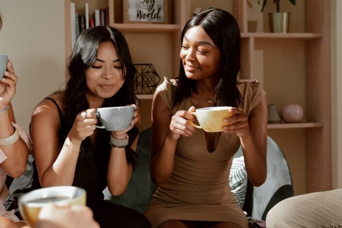 Two women smiling while drinking from mugs