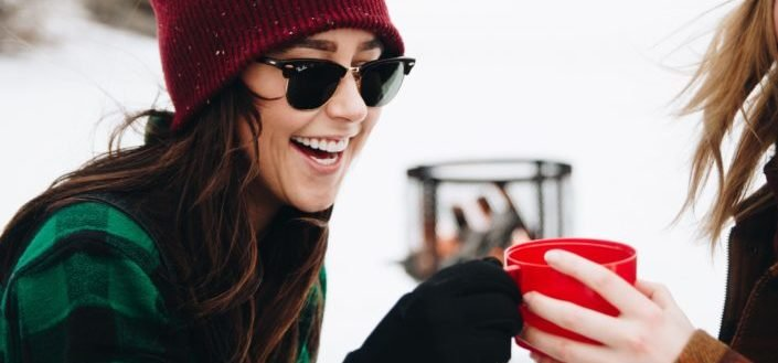 A woman wearing sunglasses laughing
