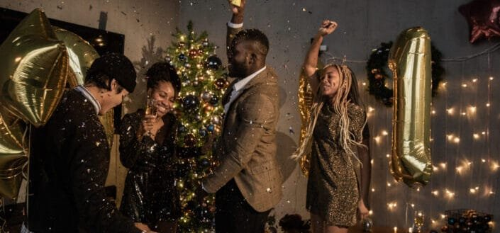 a group of friends dancing near a christmas tree