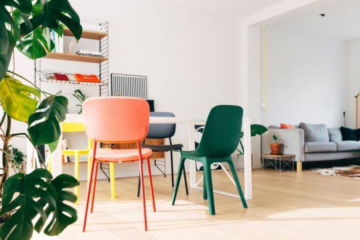 an empty room with colorful chairs and a table