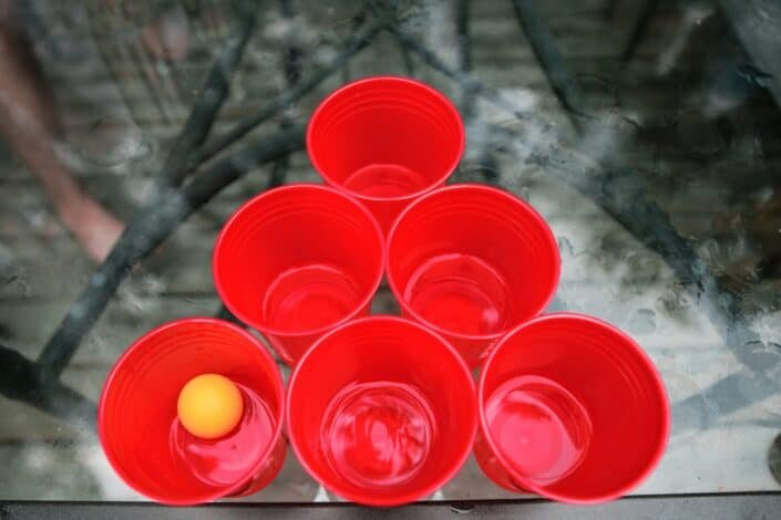 6 red plastic cups with a ping pong ball inside of one