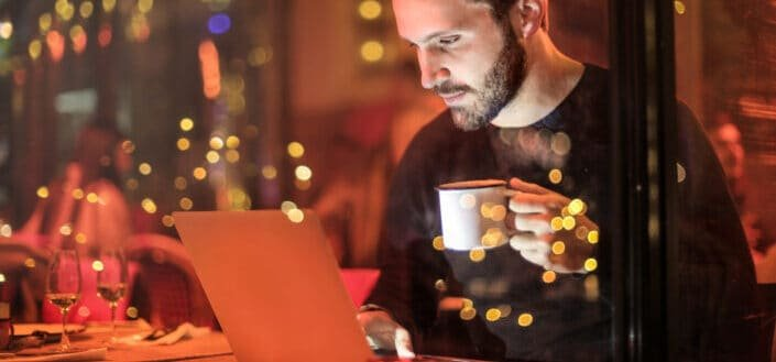 man holding a cup of coffee while looking at his laptop