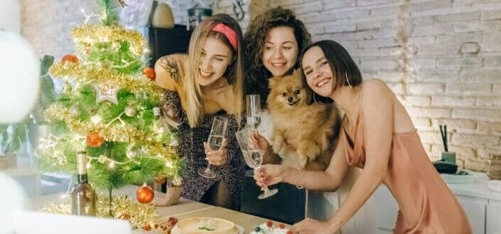 three women and a dog smiling in front of a small christmas tree