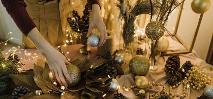 a woman's hand fixing christmas decorations