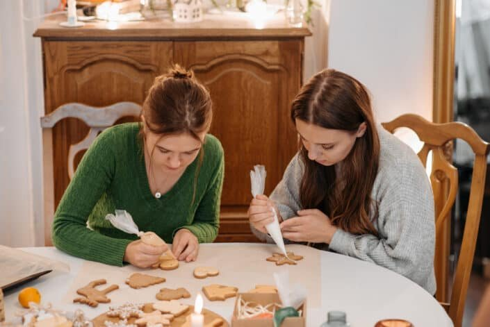 two women decorating christmas cookies