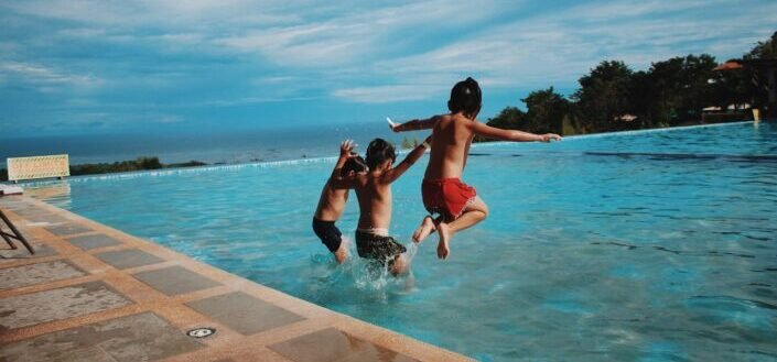 three little boys jumping into a pool