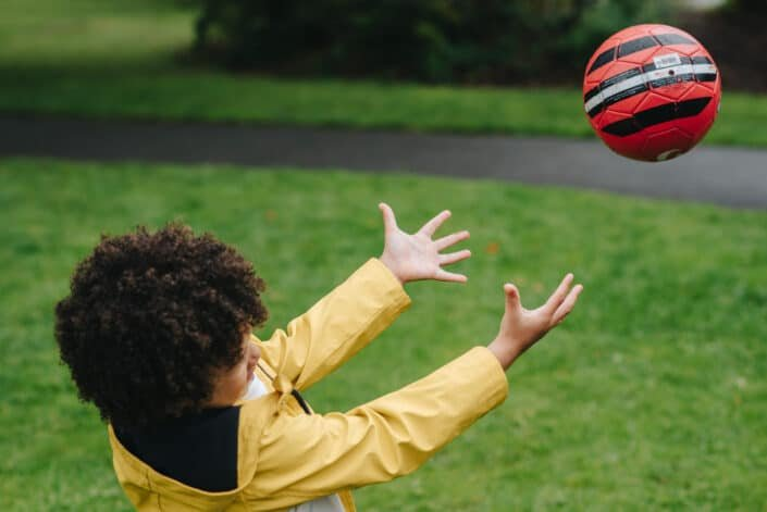 curly haired boy throwing soccer ball