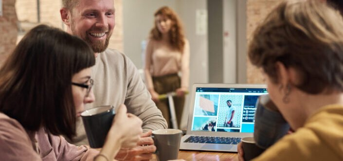 smiling guy presenting to couple sipping coffee