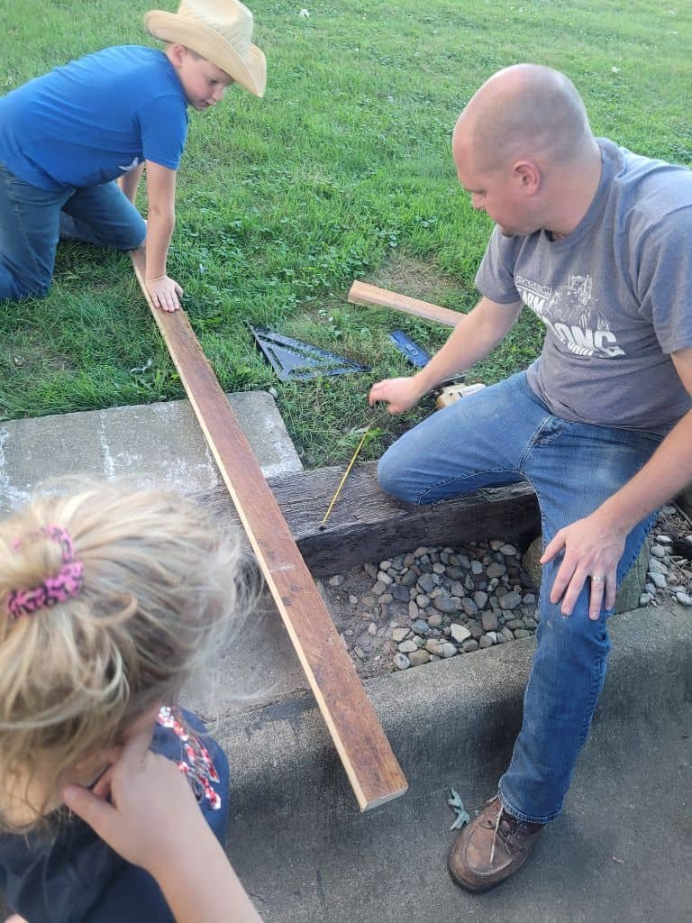 photo of a father and his son and daughter measuring wood for a shelf
