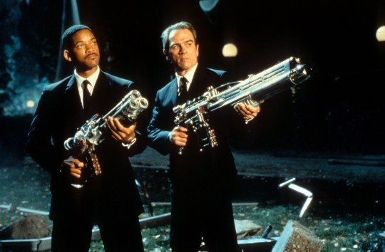 Will Smith and Tommy Lee Jones aiming their weapons towards the sky in a scene from the film 'Men In Black'