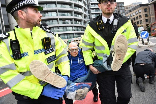 A climate activist from the group Insulate Britain is arrested and carried away by police during a demonstration in which they blocked a round about calling for the UK government to fund the insulation of Britain's homes in central London on October 8, 2021. - Climate activist group Insulate Britain blocked roads in central London and the M25 motorway on October 8, 2021 in the latest action in their campaign to demand that the UK government funds a programme to insulate Britain's homes, starting with the homes of the poorest people in the country, amid a looming climate crisis. (Photo by Daniel SORABJI / AFP) (Photo by DANIEL SORABJI/AFP via Getty Images)